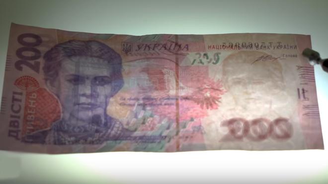 """Как отличить """"на глаз"""" фальшивые 200 гривен: ВИДЕОинструкция"""